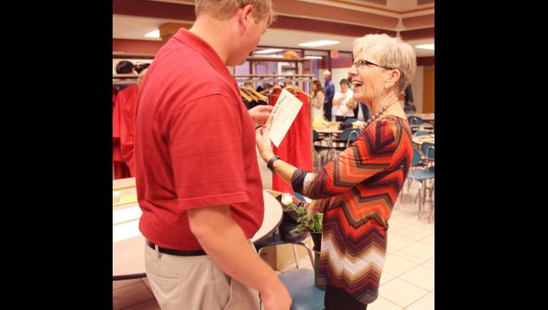 Luverne High School secretary Diana Ouverson hands new graduate Casey Klosterbuer his signed diploma after commencement exercises Sunday in the elementary school commons.