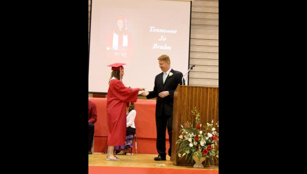 Tennessee Bruhn hands principal Ryan Johnson a ball bearing as she receives her diploma.
