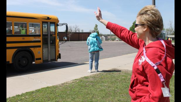 Luverne Elementary School Principal Stacy Gillette does her customary good-bye wave to students on the last bus leaving the parking lot Wednesday, May 13, on the last day of school before the summer break.