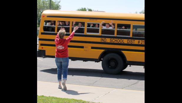 Elementary students in Luverne enthusiastically wave their hands out the bus windows (they had permission from the driver) to Principal Stacy Gillette as their bus leaves the parking lot on the last day of school.
