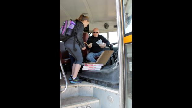Luverne Public School bus driver Mike Jarchow (right) treats Anna Huisman and the rest of his riders to a slice of pizza on the last day of school Wednesday. Students were dismissed for the summer at 11:30 a.m., right before lunch.