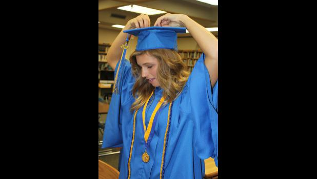 Brooke Echter works on fitting her graduation cap just before the Adrian High School commencement program begins Friday, May 15.