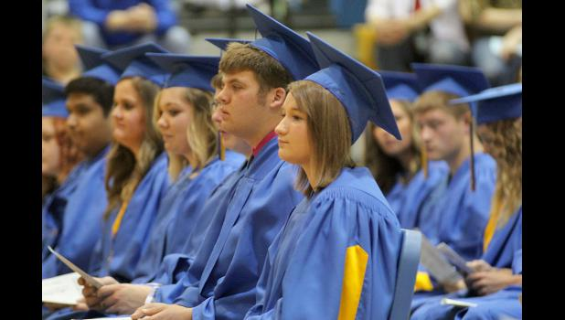 Graduates Quinn Cleveland (left) and Erica Diekmann, right, patiently wait for their diplomas during ceremonies at Adrian High School's graduation.