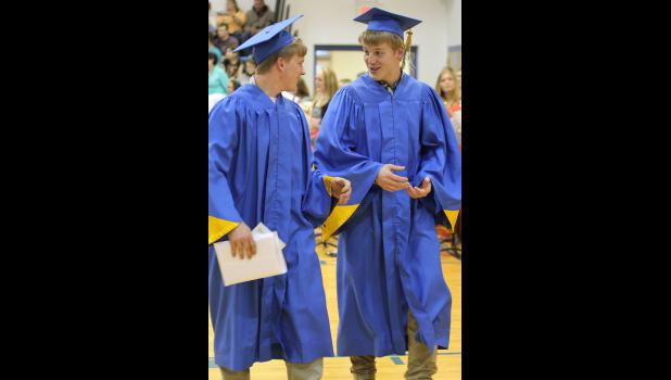 Carter Van Dyke (left) and Jesse Slater make their way to the receiving line after commencement.