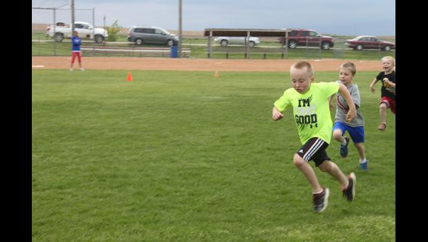 First-grader Gavyn Leuthold runs to the finish line at the H-BC Puppy Relays Friday, May 15.