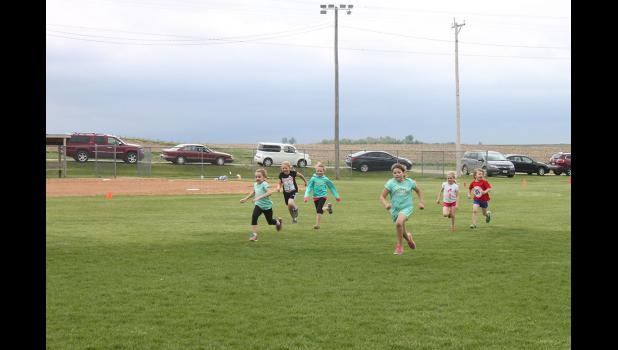 First-grader Isabel Wysong runs to the finish line during H-BC puppy relays Friday, May 15.