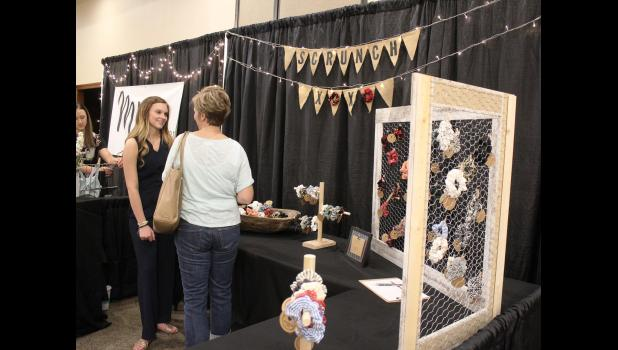 Courtney Fey (left), a student at Edgerton High School, is one of 16 high school students participating in the first Southwest Minnesota Creating Entrepreneurial Opportunities. In a CEO showcase event Wednesday evening, May 15, in Luverne, Fey displayed her business, ScrunchOXOX, to visitors like Kristi Scholten from Hills.