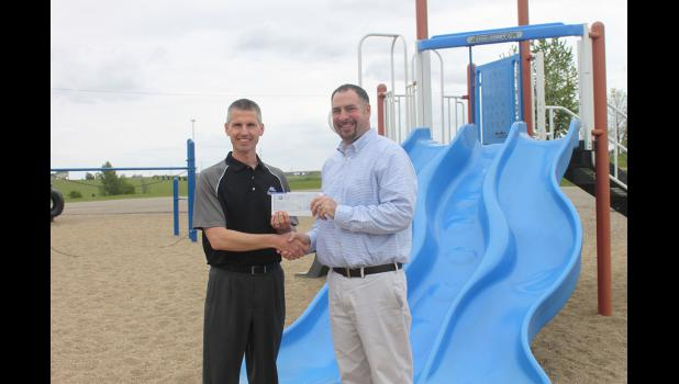 Alliance Communications representative Paul VanDeBerg (left) presents Hills-Beaver Creek Elementary Principal Jason Phelps with a check for $5,500. The money will be used for the playground resurfacing project.