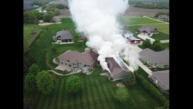 "Luverne drone operator Ryan Gee shared this aerial view of the fire that destroyed a shop near the home of Mark and Amy Overgaard in the Rowe Drive neighborhood where Luverne Fire Chief David Van Batavia also lives. In the short amount of time it took for crews to arrive, the nearby garage had heated to the point that the inside blinds started melting, and the exterior panes of the garage and house windows began to shatter from the heat. ""If those inside panes had popped, it would have been hard to save the"