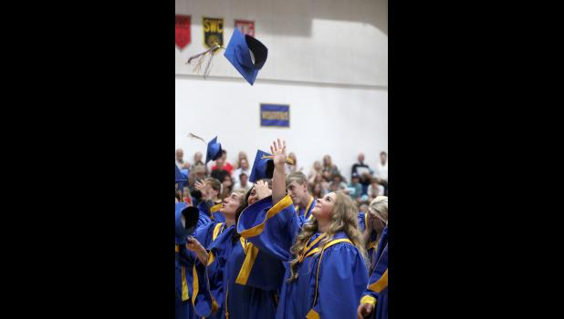 Adrian's   Alexia Kemper tosses her graduation cap at the end of ceremonies.