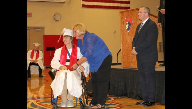 Trenton Bass receives his diploma from his aunt and board member Lois Leuthold. Bass was injured in a Sept. 8, 2017, f