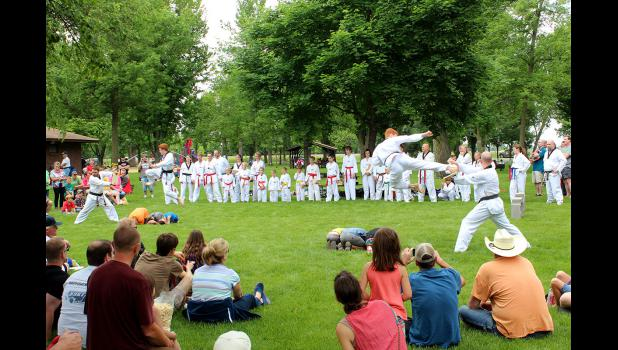 Members of Luverne Tae Kwon Do demonstrate flying side kicks over the top of volunteers lined up on the ground at the City Park Saturday.