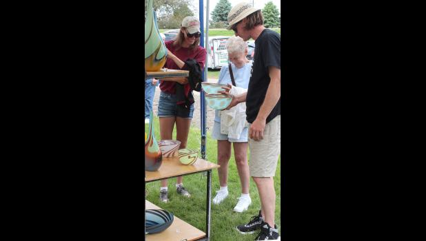 Luverne native Tom Maras sells hand-blown glass from his booth at Arts in the Park Saturday afternoon. He's pictured with Barb (right) and Bees (Gits) Hacket, Luverne.