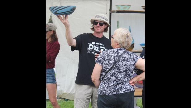Luverne native Tom Maras holds up a piece of hand-blown glass for Pauline Arhendt to see the light reflect through it.