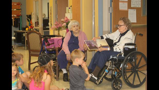 Tuff Home resident Lucille Gangestad, a former third-grade teacher, reads a book to young children during Story Time in the Tuff Memorial Home Friday, June 5.