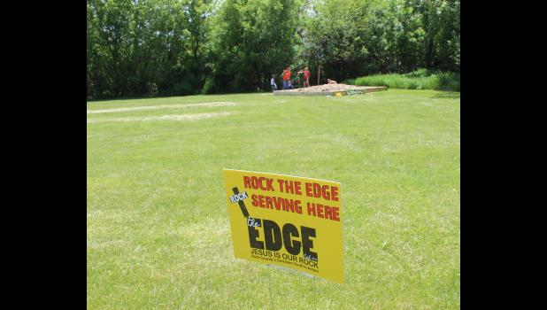"Yellow yard signs depicted where Rock the Edge youth group members were completing ""Service Over Self"" projects, such as building a sandbox at Mead Court mobile home park in Luverne."