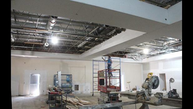 General Contractor Dan Hamann works on the ceiling drywall in the main room of the Grand Prairie Events Center Friday.