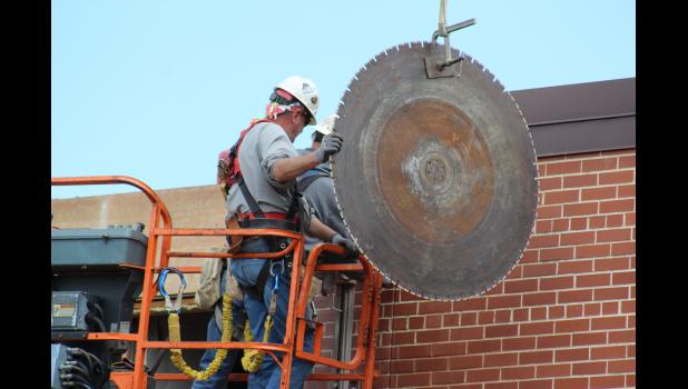 Joel Farrell (left) and Jim Hoiten with Gil Haugan Construction of Sioux Falls position the 48-inch saw blade into position Thursday morning, June 13, at the Luverne Middle-School High School.