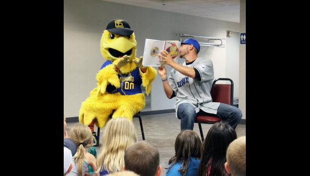 "Sioux Falls Canaries mascot ""Cagey"" (left) reacts to the picture from the book ""Slugger"" as read by his teammate, pitcher Josh Ferrell."