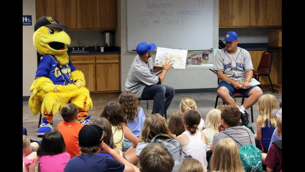 More than 50 people attend the special library event featuring members of the Sioux Falls Canaries baseball team. Pitcher Josh Ferrell (center) reads while teammate Billy Waltrip (right), also a pitcher, and Cagey, the team mascot, listen.