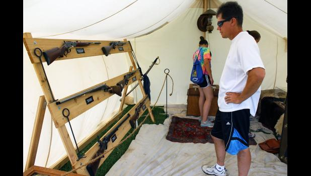 Roger Wynia of Luverne inspects guns on display Saturday inside the Roosevelt tent.