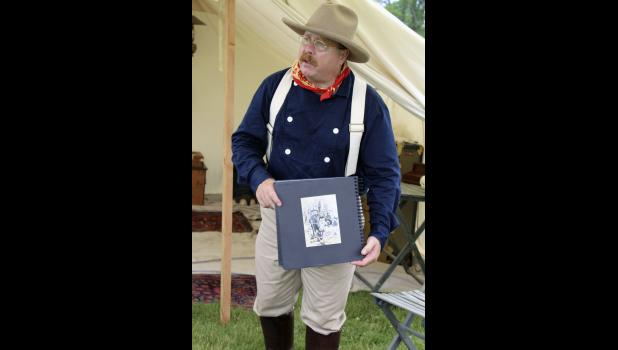 Adam Lindquist portrays Theodore Roosevelt and holds a photo album depicting a picture drawn by a journalist of the president who refused to shoot a bear while on an exhibition.