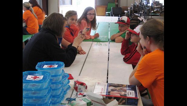 Rock County 4-H Ambassador Mary Christians (far left) and Michaella Sandbulte (far right) help participants make a list of common items to be included in a first-aid kit. Christians later demonstrated the proper way to administer cardiopulmonary resuscitation (CPR) techniques with participants.