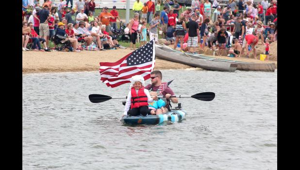 Brad Fransen paddles the kayak as young George Washington (Oliver Mead) entertains crowds in the Parade on the Pond. The entry won first place in the children's division.