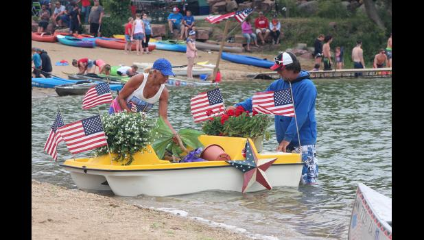 "Patricia Scheidt and Tom Nelson decorate their paddleboat for the Parade on the Pond. They called their entry ""Flowers of Freedom."""