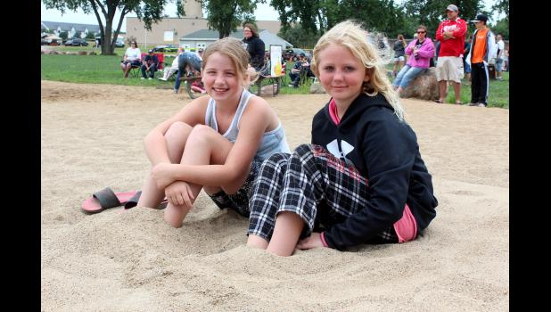 Hailey Boll (left) and Veronica West bury their toes in the sand on the beach at The Lake.