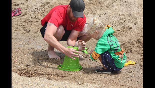 Aaron Altman and 4-year-old Braylynn Altman work on their sandcastle entry.