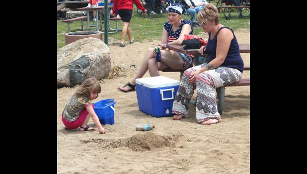 Jaeva Evans builds her sandcastle with an audience, Fawn Rustand (left) and Nicole Hartke.