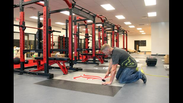 Nathan Meyer with Push-Pedal-Pull of Sioux Falls rolls down the new Cardinal emblem last week in the recently completed weight room in the former Luverne Middle-High School band and choir rooms.