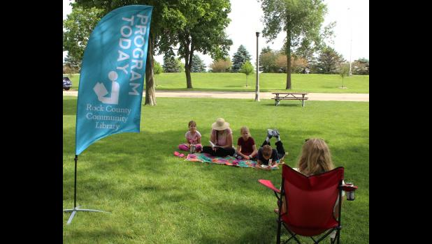 """The McCrary family joined Rock County Community Library Director Calla Jarvie (in chair) at the library's first """"Peaceful Park Summer Book Club"""" event July 3 at the Luverne City Park. Pictured on the blanket from left are Ella, Shannon, Joyce and Evan McCrary."""