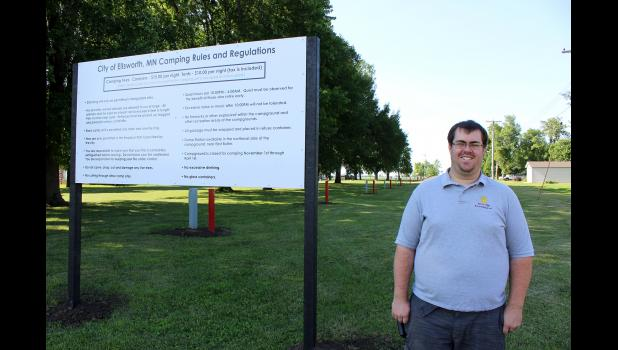 Ellsworth City Councilman Spencer Swanson stands in front of signage for the newly developed campground in Ellsworth. The project began three years ago when the city received a grant to purchase new restroom equipment.