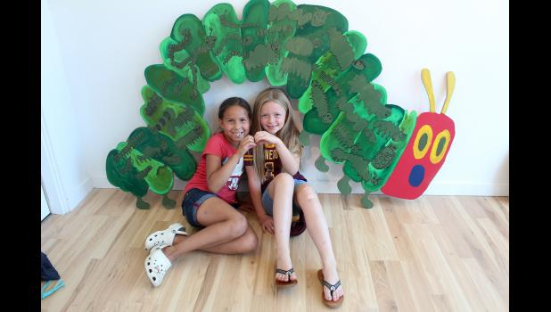"""Isley Smith (left) and Emersyn Klosterbuer, both 7, pose underneath their artistic contributions to the """"Expression is Elementary"""" exhibit at Lord Grizzly Gallery in Luverne Thursday, July 11. They submitted drawings related to the book, """"The Very Hungry Caterpillar,"""" by Eric Carle."""