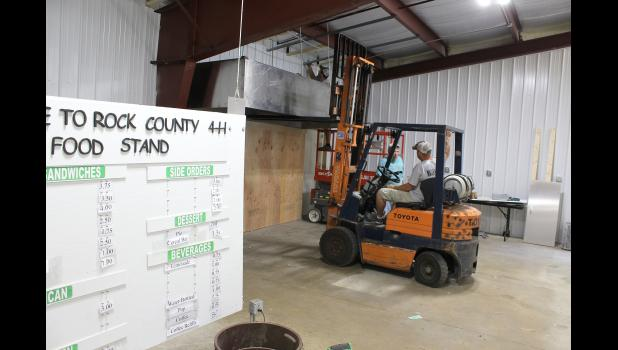 The 4-H food stand at the Rock County Fairgrounds in Luverne is receiving a makeover in preparation for this year's county fair July 25-28. On Wednesday morning, July 11, Busse Plumbing and Heating workers hung the new grill hood. Pictured are Tyler Williams (left on scissor lift), Lyle Nelson and Anthony Mann (in forklift).