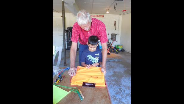 Mentor George A. Bonnema and Little Buddy Will Soto work on decorating a cinch bag.