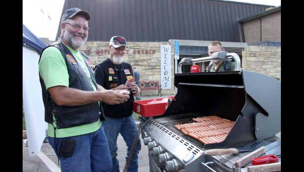 Bill Spieker of Lismore and Jim Vanderburg of Manley load the grill with 120 hot dogs. The Christian Motorcycle Association gave out 400 hot dogs by night's end.
