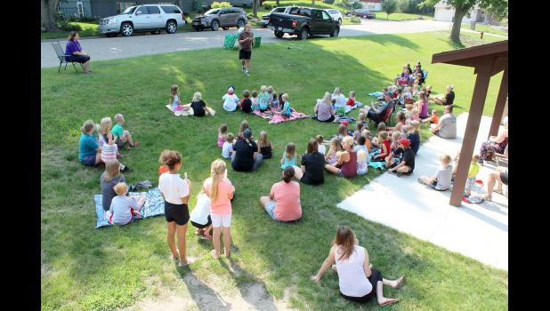 """Dozens of children and adults gather at Hawkinson Park in Luverne Thursday morning, July 22, for the Rock County Library sponsored program """"Zoo Man at the Park"""" with Brent Mielke (top) holding a corn snake for audience members to see and later touch."""
