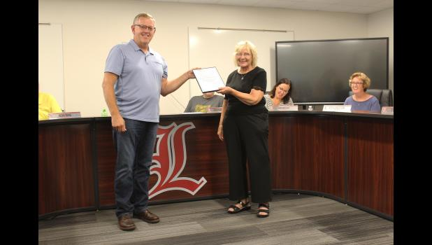 """Saturday, July 31, is """"Marlene Mann Day"""" in honor of the Luverne Public School business manager's 55 years with the district. Luverne Mayor Pat Baustian (left) presented Mann with a copy of the proclamation Thursday night, July 22, at her last Luverne School Board meeting."""