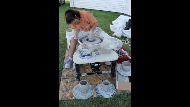 Luverne artist Cindy Reverts demonstrates using a pottery wheel, displaying several of her creations Friday.