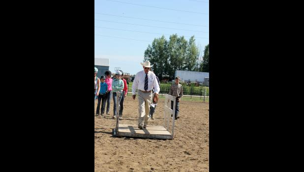 Luverne native and horse judge Joe Rowe walks over the bridge at Friday's horse show as he demonstrates the elements of the trail class to intermediate and junior horse exhibitors.