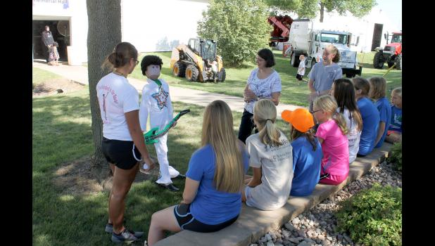 "Judge Carol Christopherson talks with the Blue Ribbon 4-H Club members about their scarecrow entry ""Rock County Fair Rocks"" Wednesday afternoon, July 29, during entry day for club and perishable item exhibits."