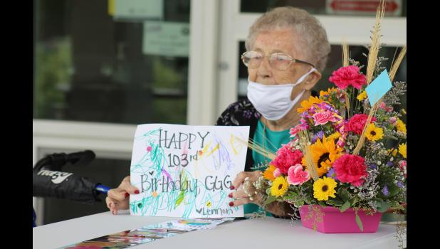 Madge May holds the birthday card colored by her great-great-granddaughter Lennon Zwaan with great-granddaughter MacKenzi Zwaan writing the message for the 2 1/2-year-old.
