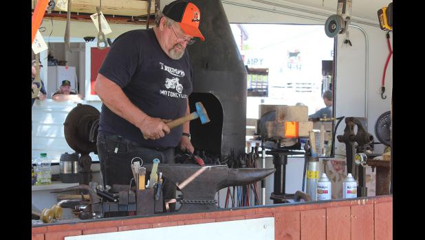 Larry Wasmund of Pounded Treasures, St. Paul, demonstrates the lost art of blacksmithing at the Rock County Fair Thursday afternoon, July 30.