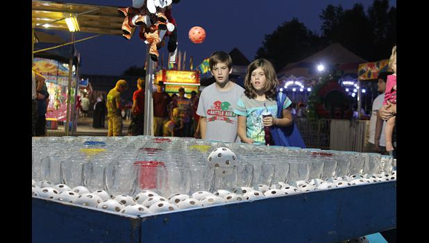 Bridget and Levi Thielbar watch as their ball bounces off the rims of glasses during a midway game at the Rock County Fair.