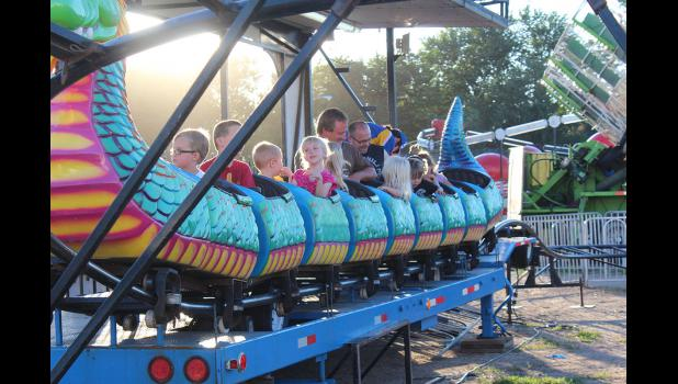 Young riders buckle their seatbelts on the dragon roller coaster ride at the fair Thursday night.