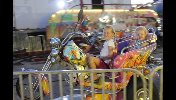 Hadley (front) and Emery Vanderburg enjoy a motorcycle ride on the midway at the fairgrounds Thursday night. Their sister, Trinley (not pictured), was in the car behind them.