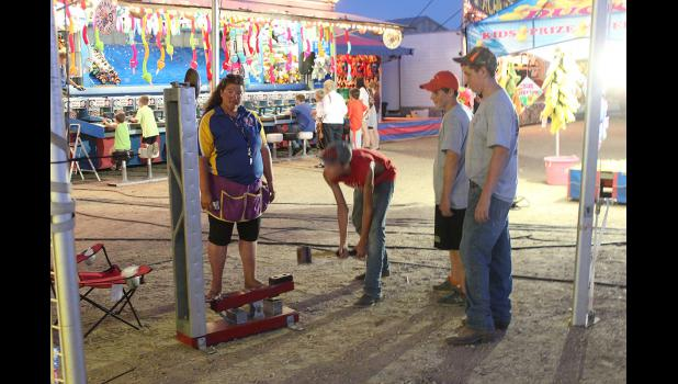 Trevor Mente lowers the sledgehammer to ring the bell at a midway game on the Rock County Fairgrounds Thursday night.